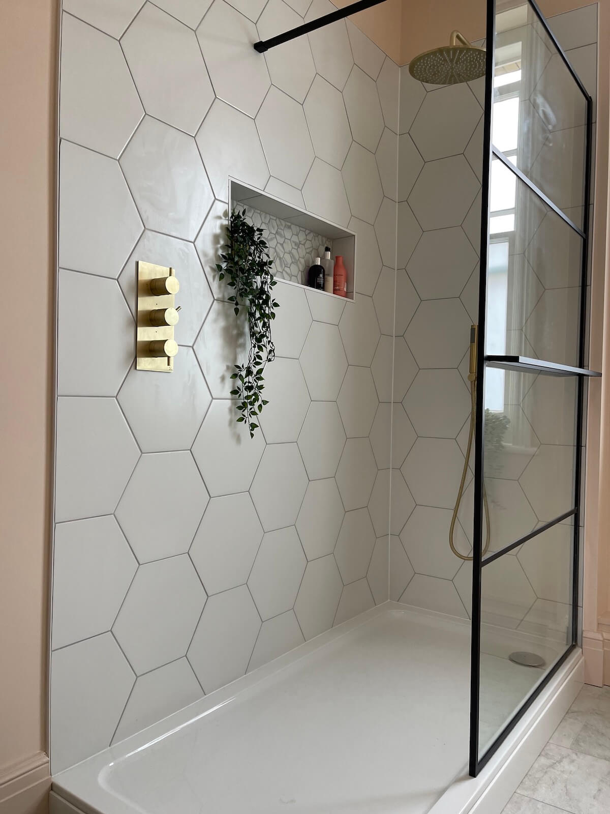 Shower with brass taps and hexagon tiles